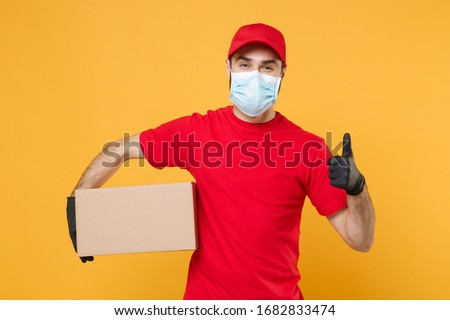 Delivery man employee in red cap blank t-shirt uniform face mask gloves hold empty cardboard box isolated on yellow background studio Service quarantine pandemic coronavirus virus 2019-ncov concept Royalty-Free Stock Photo #1682833474