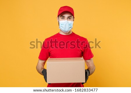 Delivery man employee in red cap blank t-shirt uniform face mask gloves hold empty cardboard box isolated on yellow background studio Service quarantine pandemic coronavirus virus 2019-ncov concept #1682833477