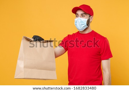 Delivery man employee in red cap t-shirt uniform mask glove hold craft paper packet with food isolated on yellow background studio Service quarantine pandemic coronavirus virus 2019-ncov concept #1682833480