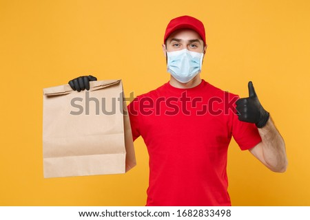 Delivery man employee in red cap t-shirt uniform mask glove hold craft paper packet with food isolated on yellow background studio Service quarantine pandemic coronavirus virus 2019-ncov concept #1682833498