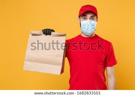 Delivery man employee in red cap t-shirt uniform mask glove hold craft paper packet with food isolated on yellow background studio Service quarantine pandemic coronavirus virus 2019-ncov concept #1682833501