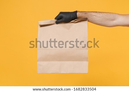 Close up male hold in hand glove brown clear empty blank craft paper bag for takeaway isolated on yellow background. Packaging template mockup. Delivery service concept. Copy space Advertising area #1682833504