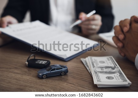 Agent car salesman is explaining about the new car purchase contract and agreement to the car buyer. #1682843602