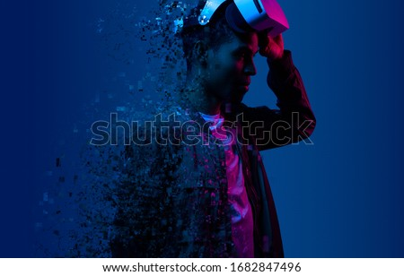 Modern ethnic guy taking of VR goggles and dissolving into particles during transition into cyberspace against blue background