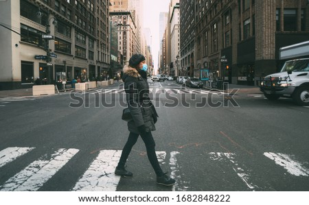 Woman wearing surgical mask going through crosswalk in midtown manhattan.Concept of Coronavirus, COVID-19 and quarantine Royalty-Free Stock Photo #1682848222