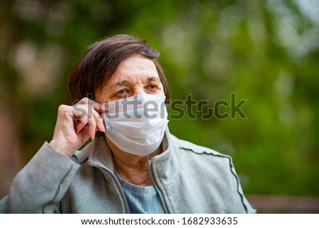 an adult woman, a pensioner, on a walk in a medical mask  #1682933635
