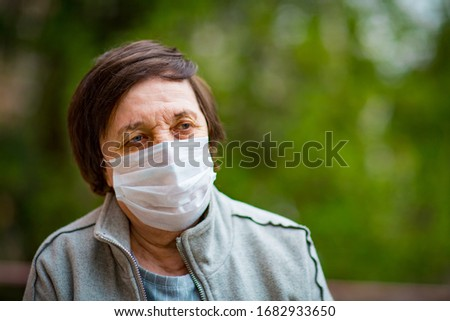 an adult woman, a pensioner, on a walk in a medical mask  #1682933650