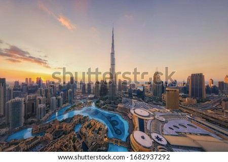 Aerial view of Burj Khalifa in Dubai Downtown skyline and fountain, United Arab Emirates or UAE. Financial district and business area in smart urban city. Skyscraper and high-rise buildings at sunset. Royalty-Free Stock Photo #1682937292