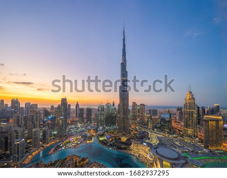 Aerial view of Burj Khalifa in Dubai Downtown skyline and fountain, United Arab Emirates or UAE. Financial district and business area in smart urban city. Skyscraper and high-rise buildings at sunset. Royalty-Free Stock Photo #1682937295