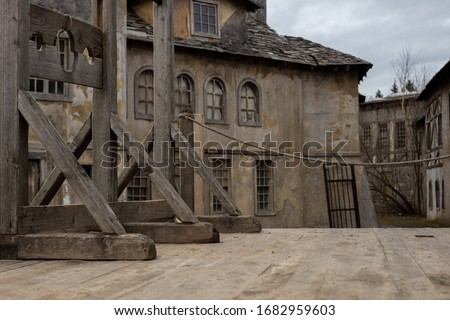 The photo shows part of a dark medieval or pirate town with a guillotine on a wooden platform. In the background, houses with broken windows, desolation and destruction as during the plague pandemic. Royalty-Free Stock Photo #1682959603