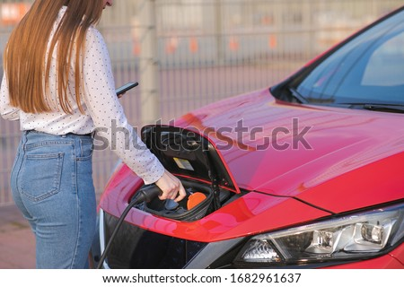 Woman Hand Attaching Power Cable To Environmentally Friendly Zero Emission Electric Car. Woman makes power supply plugged into an electric car being charged #1682961637