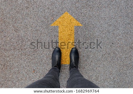 Black shoes standing on the asphalt concrete floor with yellow arrow. Feet shoes walking in outdoor. Youth Selphie Modern hipster #1682969764