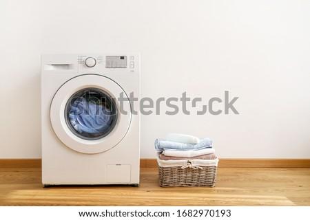 Washing machine, washing gel and laundry basket on white background Royalty-Free Stock Photo #1682970193