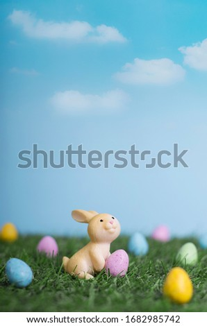 Cute little cartoon easter bunny sitting on grass among easter eggs in the garden, easter banner
