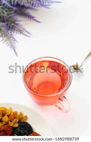 cup of herbal tea in a glass cup with a sprig of sage. medicinal natural decoction of field herbs for the treatment of colds. dried fruits - figs, plums, raisins #1682988739