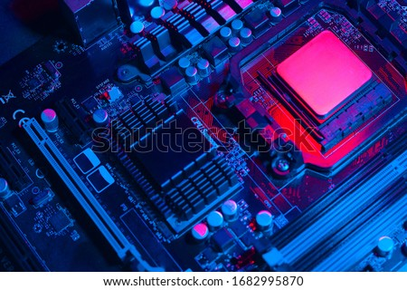 Hardware technology concept in neon light. Motherboard in blue-red light. Computer  component. Dark photo. Royalty-Free Stock Photo #1682995870