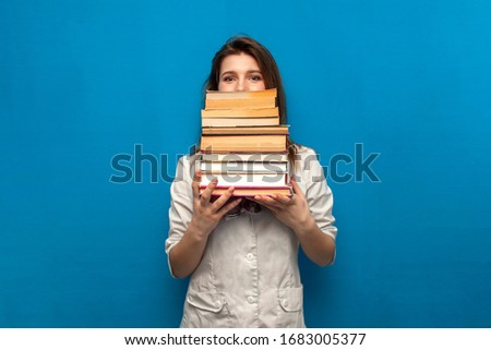 young beautiful funny girl the nurse holds many books on a blue background and is surprised, the student is studying in a medical college, copy space #1683005377