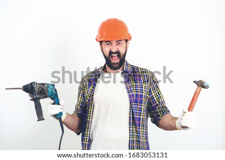 Screaming builder in helmet. Bearded man holding drill and hammer. Butal builder man. Construction worker in hard hat. Builder working with construction helmet. Builder with professional tools. #1683053131
