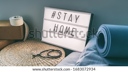 Coronavirus Yoga at home sign lightbox with text hashtag #STAYHOME glowing in light with exercise mat, cork blocks, strap meditation pillows. COVID-19 banner to promote self isolation staying at home. #1683072934