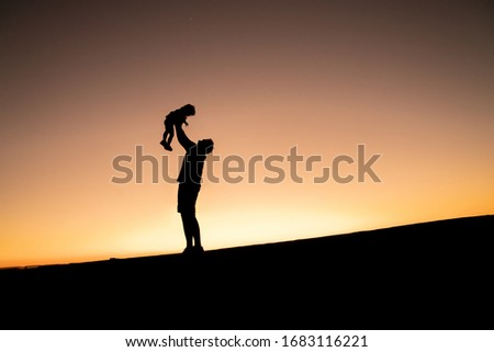 Father's day. Silhouette of a happy joyful father having fun throws up in the air little cute child baby girl on nature, sunset horizon background.