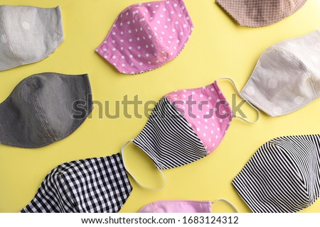 flat lay design of colorful fashion face mask handmade from fabric cloth on yellow background #1683124312