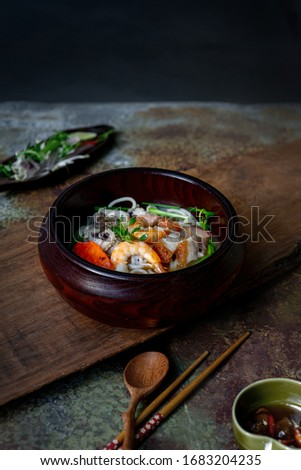 Bun Mam - street food: Vietnamese noodle soup. Fresh rice noodle cook with broth of Mekong Delta fish sauce. Topping: cat fish, fish cake, shrimps, squids, grilled pork. Serving wood vintage table. #1683204235