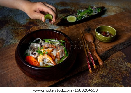 Vietnamese street food: Bun Mam - noodle soup. Fresh rice noodle cook with broth of Mekong Delta fish sauce. Topping: cat fish, fish cake, shrimps, squids, grilled pork. Serving wood vintage table #1683204553