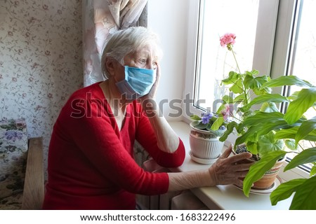 The Covid-19, health, safety and pandemic concept - senior old lonely woman wearing protective medical mask sitting near the window at home for protection from virus Royalty-Free Stock Photo #1683222496