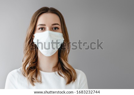 Portrait of a young woman in a medical mask isolated over grey background. Young girl patient stands against the wall background, copy space for text #1683232744