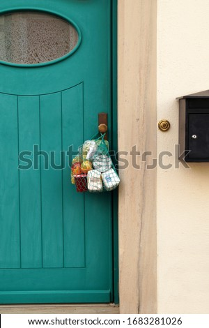 delivery during the quarantine. Shopping bag with Merchandise, goods and food is hanging at the front door, neighborhood Assistance concept at quarantine time because of coronavirus infection Covid-19 #1683281026