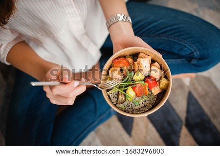 Girl holds a paper plate with healthy food sitting on the floor. Home delivery food. Healthy eating concept. When you stay at home. #1683296803
