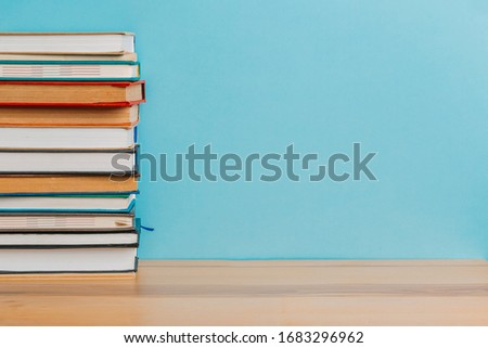 A simple composition of many hardback books, raw books on a wooden table and a bright blue background. back to school. Education. #1683296962
