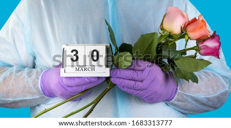 doctor with a bouquet of flowers in his hands. medical worker in surgical gown and medical gloves. Close- up of a bouquet of beautiful roses. National Doctor's Day March 30.