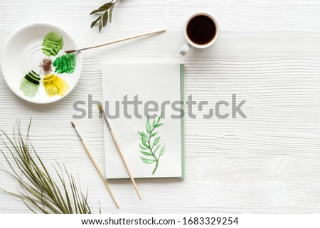 Painting herbs. Brushes and picture on white wooden background top-down copy space