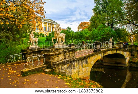 City park bridge in autumn Pavlovsk. River bridge in autumn Pavlovsk park, Russia. Park river bridge in Pavlovsk autumn. Autumn park bridge view #1683375802