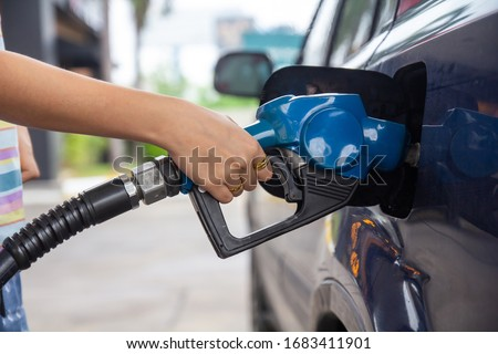 Blue car at gas station filled with fuel. Closeup woman hand pumping gasoline fuel in car at gas station.woman refuel car petrol pump filling gas at gas pump. Royalty-Free Stock Photo #1683411901