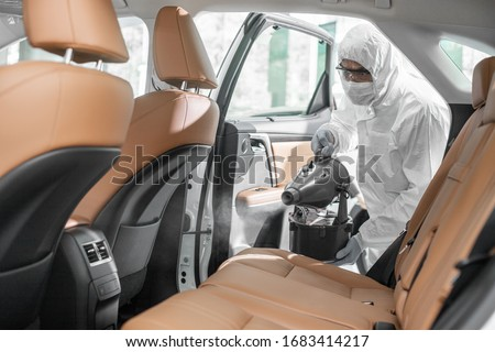 Disinfectant worker character in protective mask and suit sprays bacteria or virus in a car. #1683414217