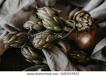 artichokes on grey background. fresh organic raw artichoke flowers in vase