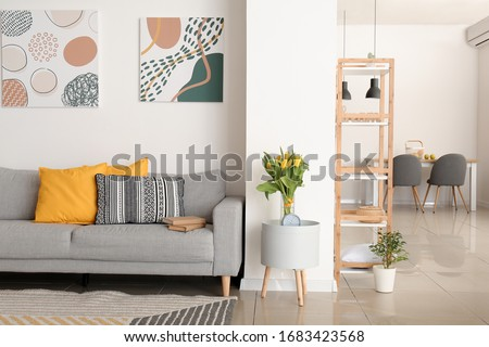 Interior of modern room with comfortable sofa and table with spring flowers