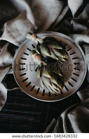 Artichoke on a plate on a light gray background. top view. artichokes on grey background. fresh organic raw artichoke flower