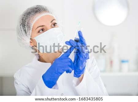 Young female nurse ready to make injection in hospital #1683435805