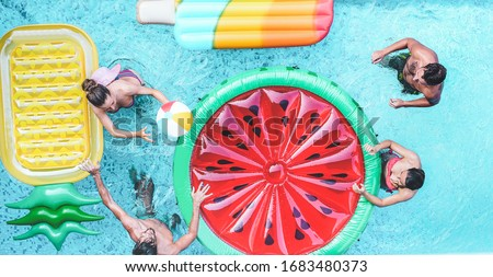 Happy friends playing with air lilo ball inside swimming pool - Young people having fun on summer holidays vacation - Travel, holidays, youth lifestyle, friendship and tropical concept #1683480373