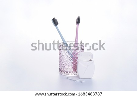 Multi-colored toothbrushes in a glass and dental floss on a white background. #1683483787