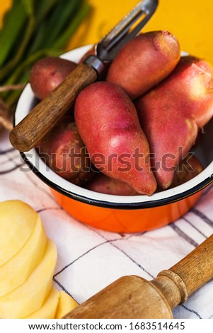 Red potatoes in a deep bowl, next to chopped potatoes. Food photo for gardeners, shops and food markets.
