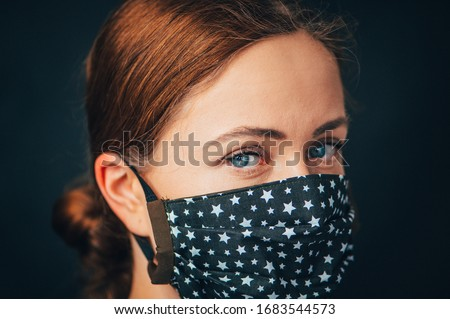 Close up woman portrait, Young woman wearing home made hygienic face medical mask to prevent infection, illness or flu and 2019-nCoV. Black background. Protection against disease, coronavirus. #1683544573