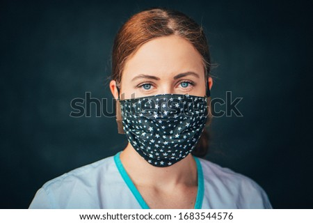 Close up woman portrait, Young woman wearing home made hygienic face medical mask to prevent infection, illness or flu and 2019-nCoV. Black background. Protection against disease, coronavirus. Royalty-Free Stock Photo #1683544576