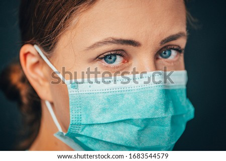 Close up portrait photo, Eye of Yong Female Doctor. Protection against contagious disease, coronavirus, hygienic face surgical medical mask to prevent infection. Black background #1683544579