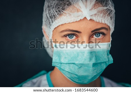 Protection against contagious disease, coronavirus. Portrait Photo. Female medical worker wearing protective face mask, head cover and suit inside hospital ward Royalty-Free Stock Photo #1683544600