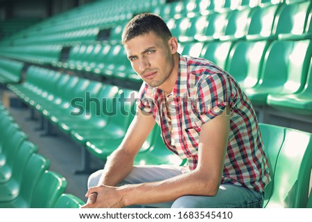 handsome and young man sitting on green chairs , sports stadium Royalty-Free Stock Photo #1683545410