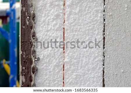 facade insulation with foam side view. a thick layer of foam on the wall for wall insulation and sound insulation. repair work on the insulation of houses close-up. #1683566335